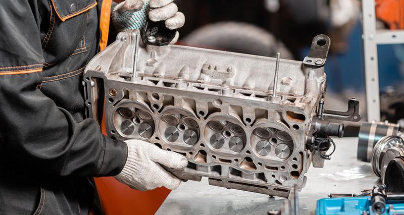 mechanik trzymający część silnika